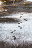 在第一雪盖的湿道路的脚印 免版税库存图片