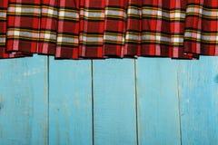 在笼子和木头纹理的纺织品 蓝色木桌 在一只笼子的布料在蓝色木纹理 在桌上的五颜六色的织品 竞争 免版税库存图片