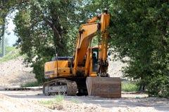 在等待卡车的大树树荫下停放的挖掘机在大工地工作装载 免版税库存照片