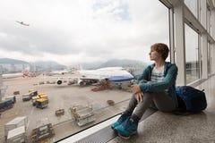 在等待她的飞行的窗口附近的女孩在机场 免版税库存图片