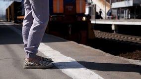 在等待火车的铁路平台的妇女的腿 在背景中火车通过  股票视频