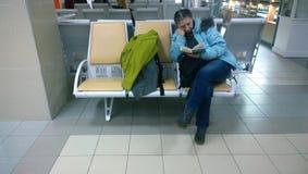 在等待离开的乏味妇女阅读书在机场 免版税库存照片