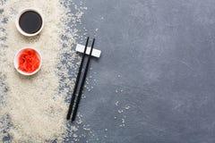 在筷子、大豆和姜的顶视图在土气灰色和白米背景 平的位置拷贝空间 图库摄影