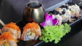 在筷子的手享用与橙色Ebiko的三文鱼寿司 股票录像