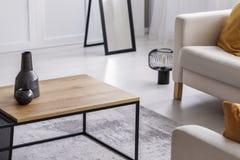 在简单的木咖啡桌上的陶瓷花瓶在典雅的客厅,真正的照片 免版税库存图片