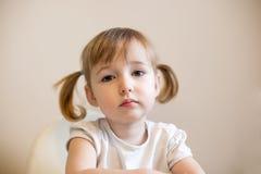 在简单的背景的小孩女孩面孔特写镜头逗人喜爱的画象 免版税库存照片