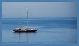 在简单的蓝色背景的船 库存照片