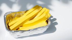 在箔包装的炸薯条在树下有阴影natu 免版税库存图片