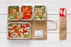 在箔容器顶视图的每日饭食交付在白色木头 库存照片