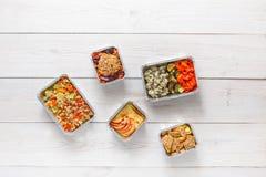 在箔容器顶视图的每日饭食交付在白色木头 免版税图库摄影
