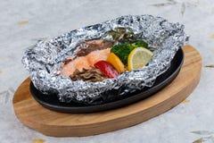 在箔的烤三文鱼包装用硬花甘蓝、甜椒、蘑菇和在木板材的热板供食的切片柠檬在washi 免版税库存照片