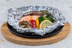 在箔的烤三文鱼包装用硬花甘蓝、甜椒、蘑菇和在木板材的热板供食的切片柠檬在washi 库存照片