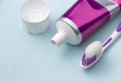 在管和牙刷的牙膏在蓝色背景 牙齿卫生学概念 免版税库存图片