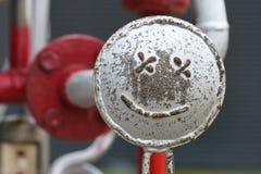 在管子建筑的兴高采烈的面孔 愉快的修理概念 库存照片
