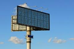 在管子的大广告牌反对天空和云彩 免版税库存图片