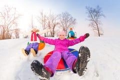 滑在管的小山下的女孩和她的朋友 免版税库存图片