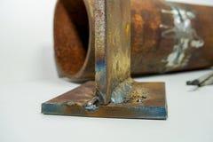 在管道和焊接处的部分的背景的焊接电极由一位专业焊工焊接证实qu 免版税库存照片