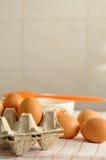 在箱子和板材的未加工的鸡蛋有垂直橙色刷子的 免版税库存图片