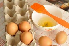 在箱子和蛋黄的未加工的鸡蛋在板材用香料和橙色刷子 免版税库存照片