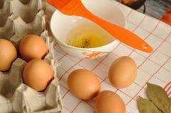 在箱子和蛋黄的未加工的鸡蛋在板材用香料和橙色刷子 免版税库存图片