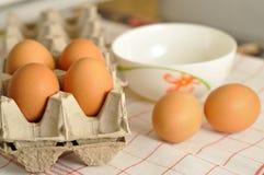 在箱子和蛋黄的未加工的鸡蛋在板材 库存照片