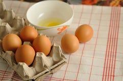 在箱子和蛋黄的未加工的鸡蛋在板材 免版税库存照片