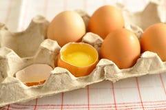 在箱子和蛋黄的未加工的鸡蛋 免版税库存照片
