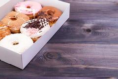 在箱子的五颜六色的油炸圈饼 库存照片