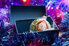 在箱子的圣诞节玩具在圣诞节闪亮金属片背景  免版税库存照片
