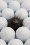 在箱子的白色和黑高尔夫球 库存图片