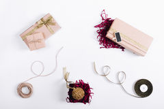 在箱子的礼物有丝带的和在一张白色桌上的圣诞节球 库存图片