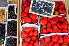 在箱子的自然草莓在农夫市场上 免版税库存照片