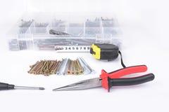在箱子的螺丝有螺丝刀和钳子的在白色 免版税库存照片