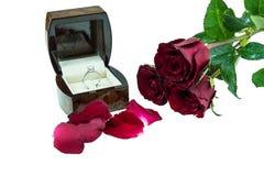 在箱子的钻戒有在白色背景的红色玫瑰的 免版税图库摄影