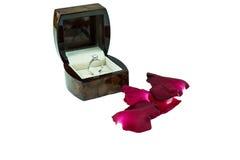 在箱子的钻戒有在白色背景的红色玫瑰的 免版税库存图片