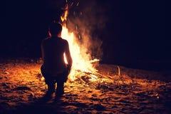 在篝火附近的男孩 库存图片