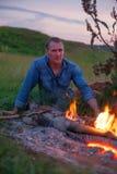 在篝火附近的逗人喜爱的人 库存照片