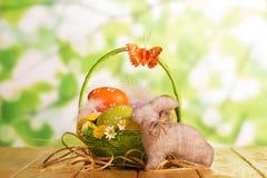 在篮子、兔宝宝和蝴蝶的复活节彩蛋在抽象绿色 库存照片