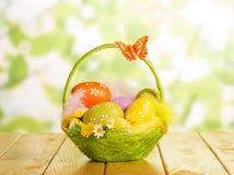 在篮子、羽毛和蝴蝶的复活节彩蛋在抽象绿色 免版税库存照片