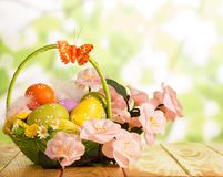 在篮子、蝴蝶和花的复活节彩蛋在抽象绿色 免版税库存照片