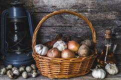 在篮子、鹌鹑蛋、大蒜、红萝卜和葱的土豆与向日葵油和老油灯 免版税图库摄影