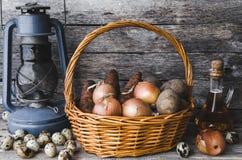 在篮子、鹌鹑蛋、红萝卜和葱的土豆与向日葵油和老油灯 库存照片