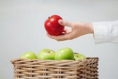 在篮子上的手用绿色苹果和红色 库存照片