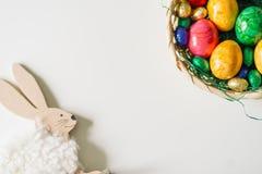 在篮子和一个兔宝宝的色的鸡蛋在一个角落作为框架 库存照片