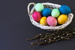 在篮子和杨柳枝杈的色的复活节彩蛋 背景上色了复活节彩蛋eps8格式红色郁金香向量 宗教基督徒假日概念复活节 免版税库存图片