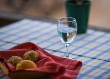 在篮子和杯的小圆面包在桌上的水 库存照片