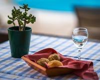 在篮子和杯的小圆面包在桌上的水 免版税库存照片