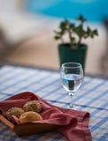 在篮子和杯的小圆面包在桌上的水 图库摄影