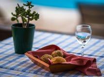 在篮子和杯的小圆面包在桌上的水 免版税图库摄影