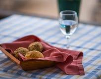 在篮子和杯的小圆面包在桌上的水 库存图片